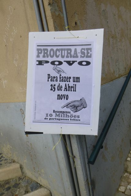 "A sign posted throughout downtown Lisbon reads, ""Wanted: People to make a new April 25. Salary: 10 million happy Portuguese."""