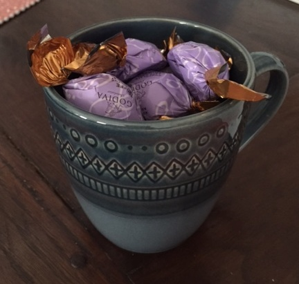 This lovely mug was filled with chocolate, but now I had to stuff paper into the bottom because I've eaten most of the candy.